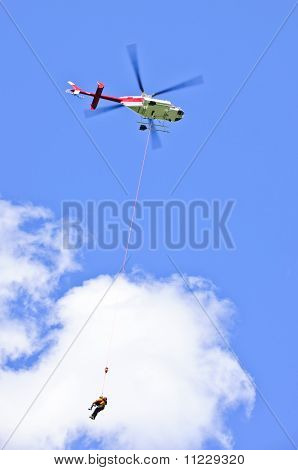 Picture or Photo of Rescue helicopter rescuing person by airlifting dangling on rope