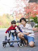 stock photo of babysitting  - Teen boy with disabled little brother in walker out walking - JPG