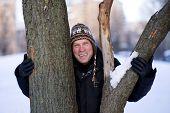 stock photo of ruddy-faced  - Happy man hugging the tree in winter - JPG