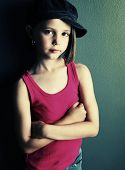 foto of newsboy  - Beautiful young female child wearing a newsboy cap and ripped jeans gray background in studio - JPG