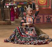 stock photo of rajasthani  - Female kalbelia dancer in traditional tribal dress performing at the annual Sarujkund Fair near Delhi - JPG