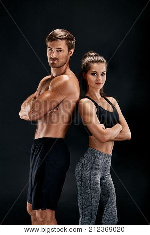 poster of Sport, fitness, workout concept. Fit couple, strong muscular man and slim woman posing on a black background. A man in shorts and a naked torso and a woman in sportswear