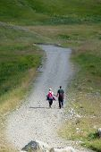 young couple of hikers with backpack walking hand in hand on stony path, Montenegro poster