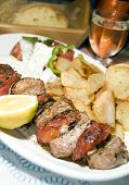 stock photo of greek food  - Pork souvlaki on skewer with tzatziki salad fried potatoes house wine crusty Greek bread as photographed in taverna restaurant Cyclades Greek island Greece - JPG