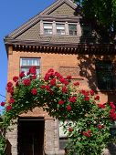 Victorian era house with gable and rose arbor