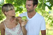 a blonde woman and a man are looking at each other, the woman is taking an apple, the background is