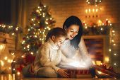 Merry Christmas and Happy Holiday! Loving family mother and child with magic gift box. poster
