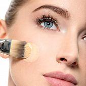 Girl applies  tonal foundation on face use makeup brush. Woman makes makeup.  poster