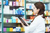 positive pharmacist chemist woman standing in pharmacy drugstore with clipboard