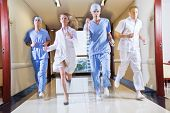 Doctor and nurse running in hallway of hospital