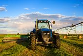 stock photo of workhorses  - Farm equipment in the field with blue sky and clouds - JPG