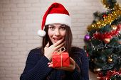 Young Cute Surprised Woman In Santa Cap Is Surprised To Get A Present. Happy Girl With A Gift Box In poster