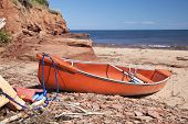 A canoe   laying on a rocky beach beside a sandstone cliff on Cabot Beach in Malpaque, Prince Edward