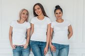 Three Young Smiling Girls In White T-shirts And Jeans On White Background. T-shirt Design. Mockup poster