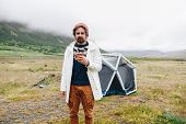 Serious Adult Man With Beard And In Red Beanie Just Woke Up At Camping Site, Come Out Of Tent In Mor poster