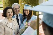 stock photo of early 20s  - Graduate Posing for Picture with Parents - JPG