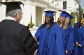 stock photo of early 20s  - Graduate Shaking Hands and Receiving Diploma - JPG