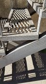 Industrial Style Metal Staircase With Lattice Steps And Geometric Shadows Underneath. Grey Painted R poster