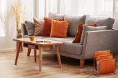 Living Room With Wooden Coffee Table And Grey Couch With Ginger, Orange And Red Pillows poster