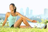 Stretching woman in outdoor exercise smiling happy doing yoga stretches after running. Beautiful hap