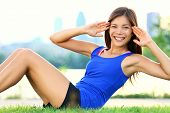 Exercise woman doing situps in outdoor workout training. Asian sport fitness woman smiling cheerful
