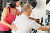 Aktiver Mensch watch Personaltrainer Maschine Pegels in Turnhalle