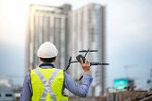Asian Engineer Man Holding Drone At Construction Site. Male Worker Using Unmanned Aerial Vehicle (ua poster
