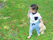 Adorable Asian Little Boy Walking With Teddy Bear At Garden Outdoor. poster