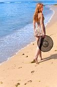 Young graceful woman goes on coast of ocean with straw hat in hands
