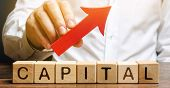Man Holds Red Arrow Up Above Word Capital. Increase Investment And Foreign Capital In The National E poster