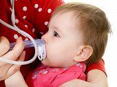 baby girl with cold and nasal aspirator on mother's hand