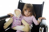 Closeup-Bild ein trauriges kleines Mädchen sitzt im Rollstuhl in ihren Pyjamas.  Sie hat eine Puppe mit band