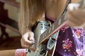 stock photo of bluegrass  - Teen girl finger picking on a banjo - JPG