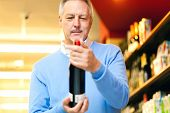 Man analyzing a bootle of red wine in a supermarket