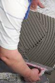 tiler at work bonding of floor  tile adhesive