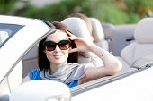 Portrait of dreamy woman wearing sunglasses in the cabriolet and propping her head