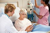 foto of geriatric  - Doctor Using Digital Tablet In Consultation With Senior Female Patient In Bed - JPG