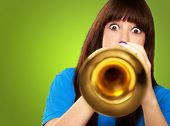 portrait of a teenager playing trumpet on green background