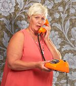 Portrait Of A Senior Woman Holding A Retro Phone On Wallpaper