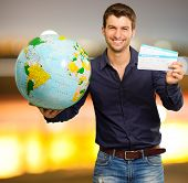 Young Man Holding Globe And Boarding Pass, Outdoor