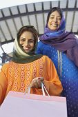 pic of dupatta  - Low angle view of an Indian woman holding shopping bag with friend in the background - JPG