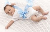 Infant baby boy in white bodysuit and blue ribbon.