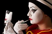 Mime performer applying Pierrot face paint with a brush