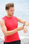 Running man looking at heart rate monitor GPS watch. Runner on beach listening to music in earphones