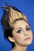 Close-up portrait of beautiful young woman with spiked hair over blue background