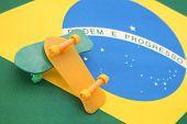 Mini plastic skateboards (Yellow and Green) over a brazilian flag. Brazilian finger skate recreation