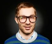 Portrait of attractive male in eyeglasses looking at camera in isolation
