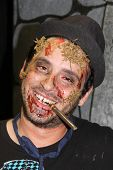MUSKOGEE, OK - Sept. 14: Actor costumed as a bloody zombie pose for a picture during the Castle Zomb