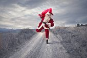 Santa Claus with big red sack runs in the country