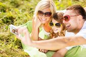 summer holidays, children and people concept - happy family with camera, blue sky and green grass ta